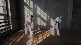 Mouvement lent garçon coréen aux cheveux foncés et un échauffement blond européen de fille dans le cours de formation Pratique en banque de vidéos