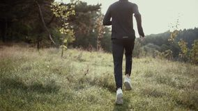 Mouvement lent Homme courant sur la colline grande d'herbe Vue arrière dépistant le tir L'appareil-photo suit le coureur de sport