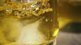 Mouvement lent l'écoulement de la boisson ambre sur le glaçon dans un verre banque de vidéos