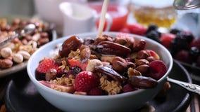 Mouvement lent : Le lait se renversant au-dessus d'un petit déjeuner des céréales avec des baies et sèchent des fruits banque de vidéos
