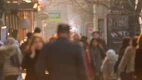 Mouvement lent Les gens marchant sur le coucher du soleil d'or de fond dans la ville Vidéo Defocused banque de vidéos