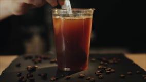 Mouvement lent Remuant avec une cuillère une pleine tasse en plastique de café froid Plan rapproch? banque de vidéos