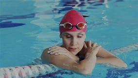 Mouvement lent superbe Jeune nageur amateur féminin détendre sur la ruelle de piscine Elle la reconstituent respirant et examinan clips vidéos