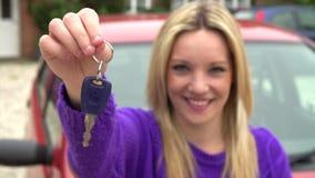 Mouvement lent tiré de la voiture se tenante prêt d'adolescente avec la clé clips vidéos