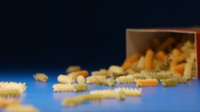 Mouvement lent : tombant une boîte avec un fusilli en spirale de pâtes de couleur - d'un côté clips vidéos