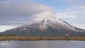 Mouvement lent - voyageur wlking à la vue regardant au volcan de taranaki en île du nord de la Nouvelle Zélande et avec banque de vidéos
