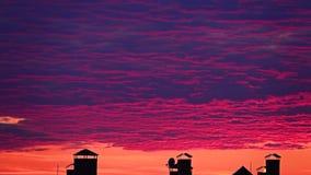 Mouvement rose de nuages de coucher du soleil au-dessus des dessus de toit de ville banque de vidéos