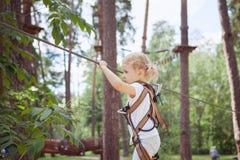 Mouvements de fille d'enfant soigneusement le long de la manière de corde photo stock