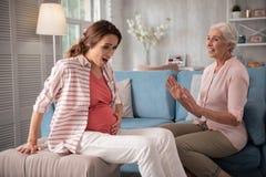 mouvements de sentiment étonnés par sentiment aux cheveux foncés de femme enceinte de petit bébé Images stock