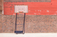 Movable basketball goal in front of bleachers. Made of red brick and concrete royalty free stock photos