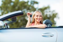 Happy young woman with convertible car key Stock Photo