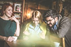 Move in game. Friends at cafe. Three young people playing leisure game at cafe. Small group people Royalty Free Stock Photography
