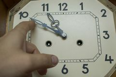 Move the hands of a large mechanical clock by hand. Close up stock photos