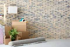 Move house concept. Carton boxes and belongings. On floor in empty room Royalty Free Stock Image