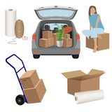Move house - estate car with opened trunk and cardboard boxes inside, boxes on the luggage cart, opened box and stretch wrap Royalty Free Stock Images