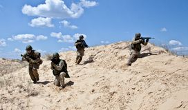 Move! Move!!. Squad of soldiers run through the desert through the military operation Royalty Free Stock Photo