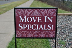 Move In Specials! Sign. Near apartment buildings Royalty Free Stock Images
