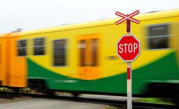 Move train. Fast move yellow regional train pass by railroad crossing Stock Image