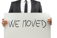 We moved. Businessman holding white board with We moved sign on it Royalty Free Stock Photo