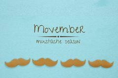 Movember cancer awareness event concept over wooden background. Top view Royalty Free Stock Photo