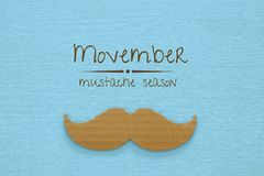 Movember cancer awareness event concept over wooden background. Top view Royalty Free Stock Images