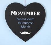 Movember fundraising for mens health awareness message on blackboard. Movember fundraising for mens health awareness charity message on black heart shape Stock Photography