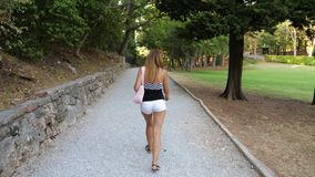 In Movement Back View Tanned Woman Walking Around The Park. In movement, back view, perfectly tanned caucasian woman walking around the park and observing the stock footage