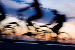 Movement of bicyclists. Movement of silhouettes of bicyclists against the dark blue sky and a sunset Stock Image