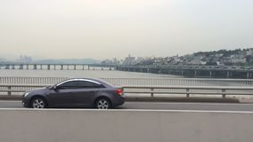 Movement on bridge over the river, high traffic. Big city life. View of a typical metropolis in Asia. Typical fast movement on the bridge by car, in the stock footage