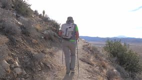 Hiking Woman Along A Mountain Path Along Cliff With The Help Of Trekking Stick. Movement of the camera following a woman hiker, she goes to the mountain path stock video