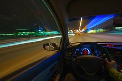 Movement of the car at night on the country highway at a high speed of viewing from the inside with the driver. Hand on. The wheel of the car. Forward movement Royalty Free Stock Photography