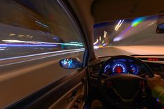 Movement of the car at night on the country highway at a high speed of viewing from the inside with the driver. Hand on. The wheel of the car. Forward movement Stock Photo