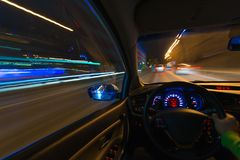 Movement of the car at night on the country highway at a high speed of viewing from the inside with the driver. Hand on. The wheel of the car. Forward movement Stock Images