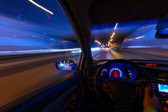 Movement of the car at night on the country highway at a high speed of viewing from the inside with the driver. Hand on. The wheel of the car. Forward movement Royalty Free Stock Images