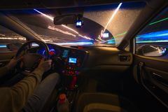 Movement of the car at night at a speed view from the interior, Brilliant road with lights with a car at high speed. Movement of the car at night when seen from Royalty Free Stock Images