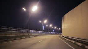 The movement of the car over the night auto interchange. View of a driver driving into a corner at the junction of a road junction stock footage
