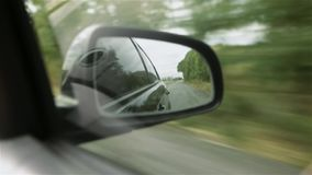 Movement in the car side mirror, view of the road. Reflection of a broken post-Soviet route with many pits. stock footage