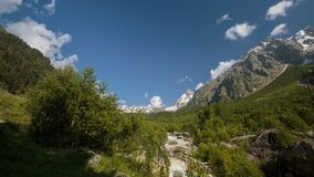 Movement of clouds and water flows in a stormy river in the Caucasus mountains in summer. Russia, time lapse. Movement of clouds and water flows in a stormy stock footage