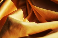 Movement and energy of texture, background. Different angles made by the folds of the golden fabric which create inner movement and energy generate the desire of Stock Photo