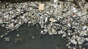 Movement of many garbage on surface of water in pond at outdoor. Of Shantou city in Chaozhou, China stock video