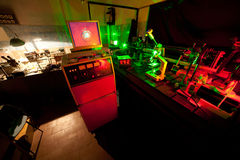 Movement of microparticles by laser in dark lab. With timer, monitor, mouse, keyboard Royalty Free Stock Photography