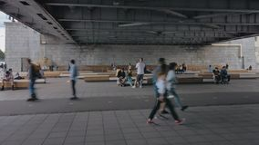 Movement of people under the bridge. Pedestrians and cyclists pass under the bridge. Some people rest on the benches stock footage