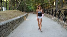 In movement pretty tanned woman walking around the park stock footage