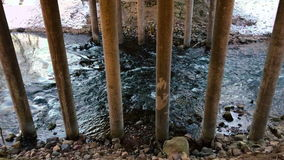 Movement of the river under the bridge in the early spring during the daytime. Side view video. Movement of the river under the bridge in the early spring stock footage