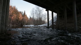 Movement of the river under the bridge in the early spring during the daytime. Video full hd stock footage