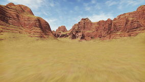 Movement through rocky canyon. Fast movement through abstract rocky canyon covered with dry grass during daytime. Realistic three dimensional animation stock footage