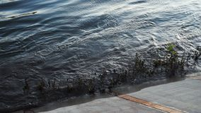 Movement of slow motion waves crush on the riverbank. Sunset reflected in rippled wave water surface