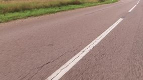 Movement of the vehicle in a two way road with white markings. Close up. Drive the car on bilateral road with a white solid and dashed markings. Close up stock footage