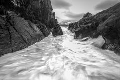 Movement of water on the shores of cold Norwegian Sea at evening time. Lofoten islands. Beautiful Norway landscape. Black-white ph Stock Photos