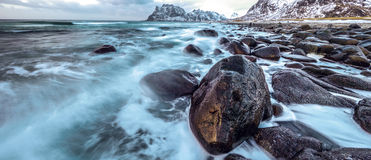 Movement of water on the shores of cold Norwegian Sea at evening time. Lofoten islands. Beautiful Norway landscape. Panoramic phot Stock Images